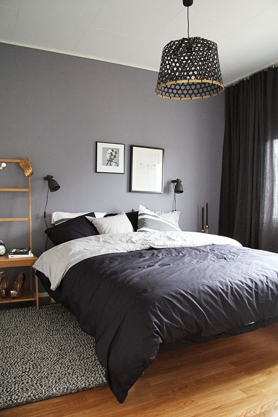 a graphite grey and black bedroom with wooden furniture, black accessories for more drama and black textiles