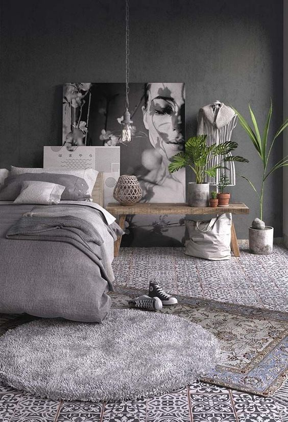 a grey bedroom with graphite grey walls, grey and white textiles and mosaic tiles on the floor and potted greenery