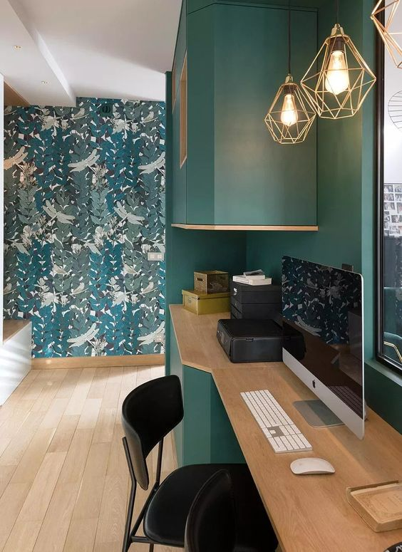 a home office space with a hunter green wall and furniture, a botanical print wall, wooden furniture and geometric pendant lamps