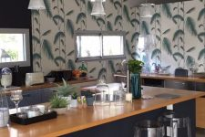a laconic tropical kitchen with tropical wallpaper, grey cabinets and a black kitchen island, wooden countertops and pendant lamps