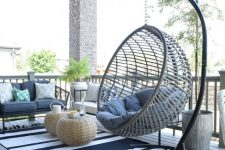 a large coastal porch with a hanging rattan chair, wicker mini tables and forged furniture, blue textiles and potted greenery