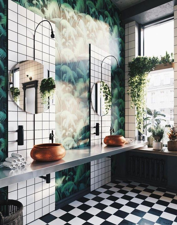 a large tropical bathroom with tropical wallpaper, white tiles, copper hammered bowl sinks and round mirrors