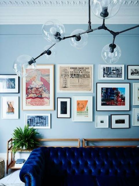 a living room with light blue walls, a gallery wall, a bright blue sofa and a catchy chandelier