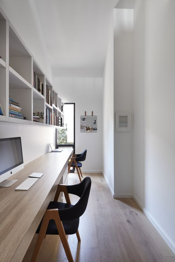 a long and narrow home office in neutrals with a floating desk and a large storage unit, a couple of blakc chairs and a tall window