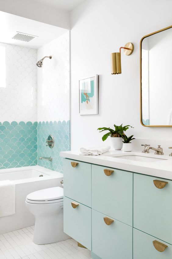 a lovely beach bathroom with mint green touches, fish scale tiles in the shower and a mint floating vanity and brass touches