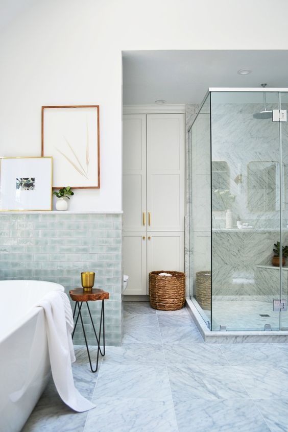 a lovely coastal bathroom with aqua glazed tiles, a shower clad with grey marble tiles, touches of wood and a basket