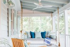 a lovely coastal porch with a hanging daybed and a lounger styled with blue printed pillows and upholstery