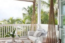 a lovely coastal porch with a suspended upholstered daybed, a rattan coffee table and neutral pillows is welcoming