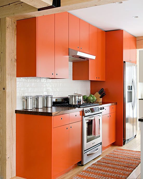 a matte orange kitchen with a white tile backsplash, a bright rug and wooden countertops is bright and cheerful