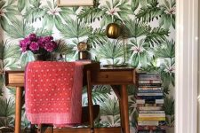a mid-century modern home office nook with a tropical wallpaper wall, elegant furniture and touches of brass