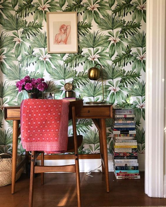 a mid century modern home office nook with a tropical wallpaper wall, elegant furniture and touches of brass