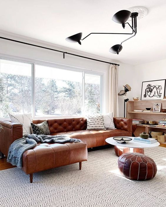 a mid-century modern neutral living room with a brown leather corner sofa and matching Moroccan poufs