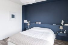 a minimalist bedroom with a navy accent wall and floating nightstands, a white bed and a pendant lamp plus an artwork