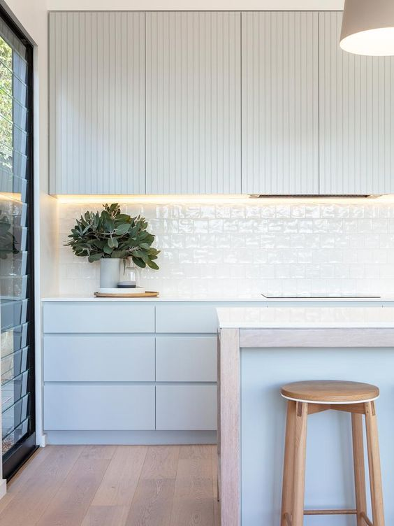 a minimalist coastal kitchen with very light blue and off-white cabinets, a white tile backsplash, a kitchen island and wooden stools