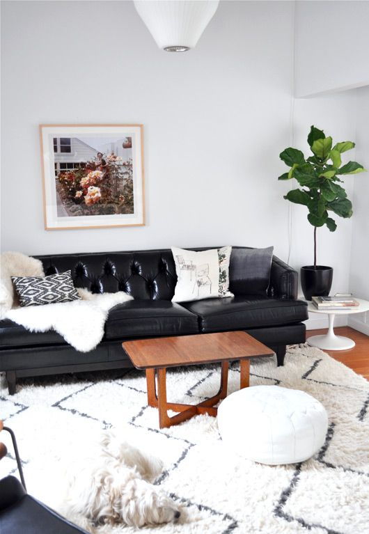 a modern Scandinavian living room with a black leather sofa, a white leather ottoman and other black and white decor for a cohesive look