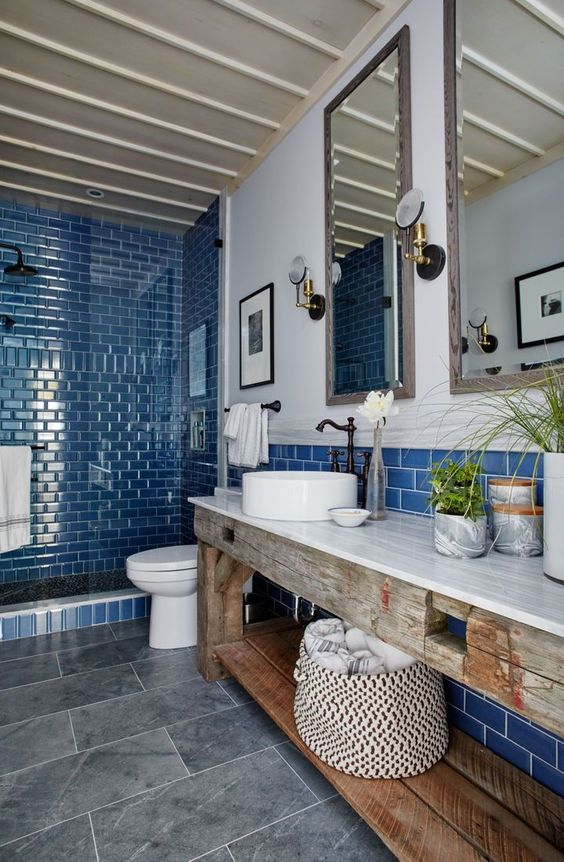 a modern beach bathroom with a shower clad with bright blue tiles, a round sink, vintage faucets and a gorgeous weathered wood vanity
