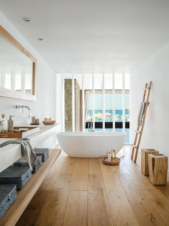 a modern beach bathroom with a wooden floor, a shelf, a ladder and stools, a floating vanity and a tub plus a gorgeous sea view