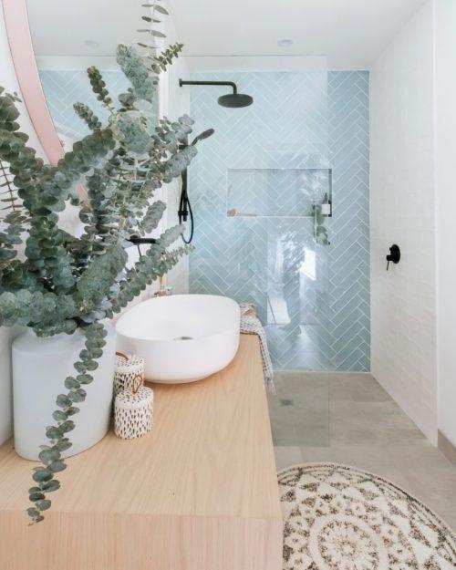 a modern beach bathroom with light blue herringbone tiles, a wooden vanity, a boho rug, eucalyptus branches and a bowl sink