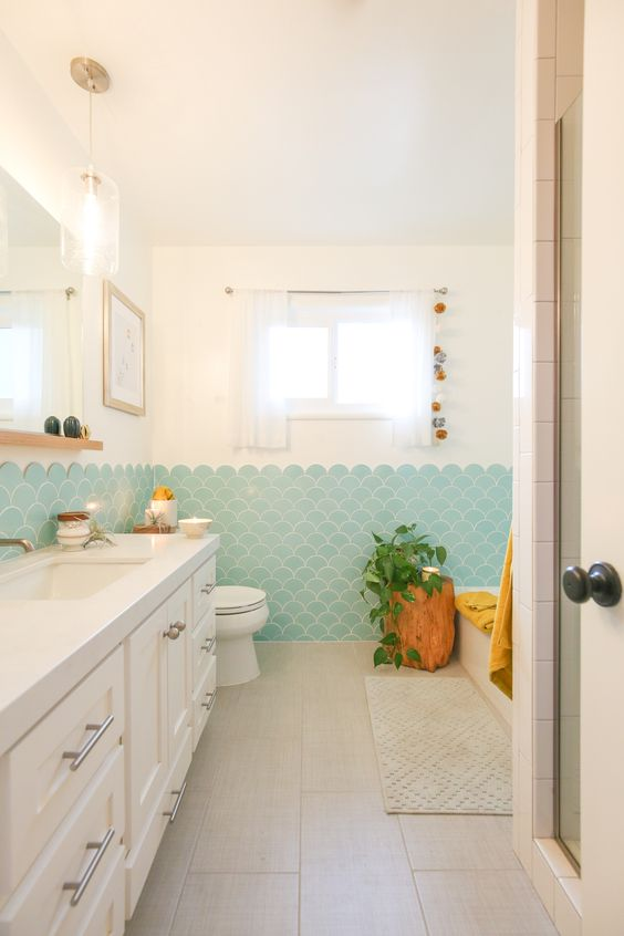 a modern beachy bathroom in neutrals, with aqua fishscale tiles, a tree stump, a large vanity and potted greenery