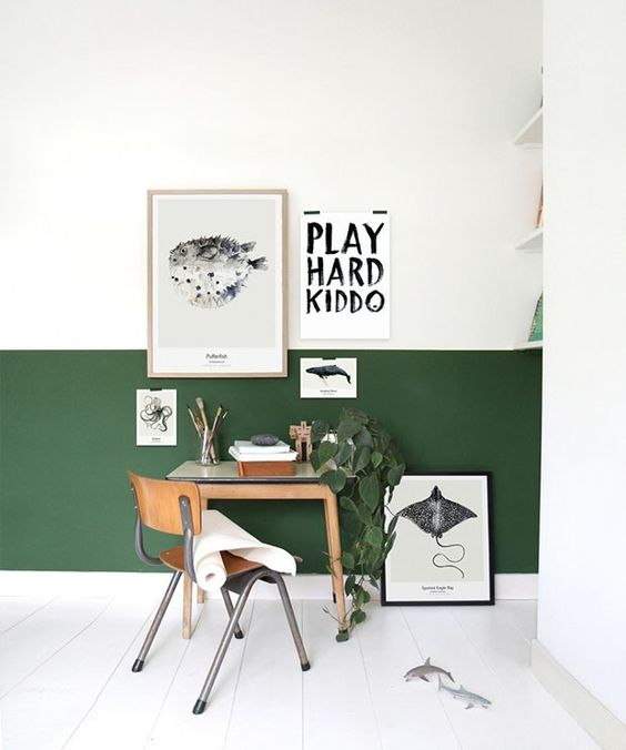 a modern color block home office with a hunter green and white wall, stylish furniture and a gallery wall and a potted plant