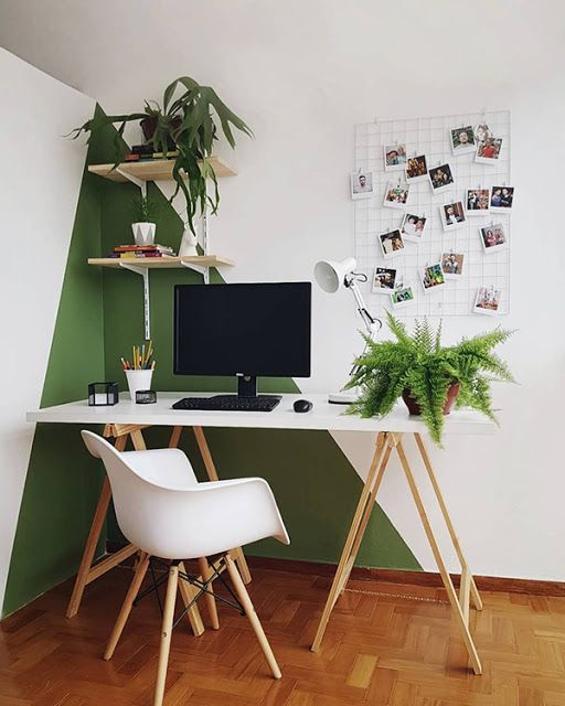 a modern home office with a color block green and white wall, white furniture, a grid and potted plants