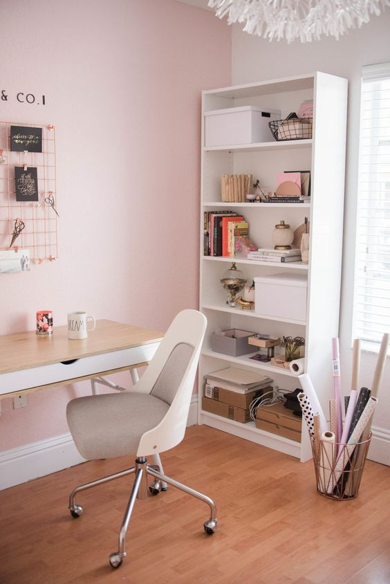 a modern home office with light pink walls, neutral furniture, a fluffy white lamp and copper touches