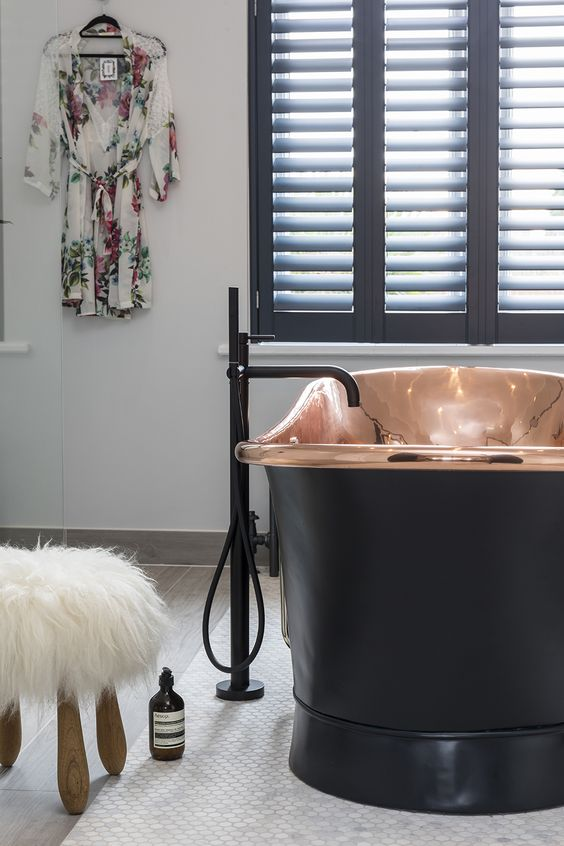 a modern luxurious bathroom with a copper and black bathtub for a statement, black shutters and black fixtures