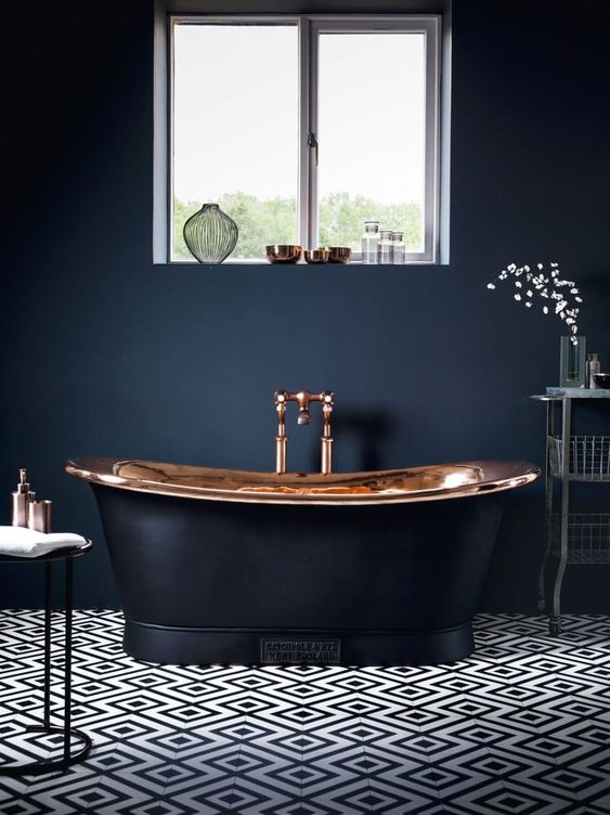 a modern luxurious bathroom with black walls, a mosaic tile floor, a copper and black tub and elegant furniture