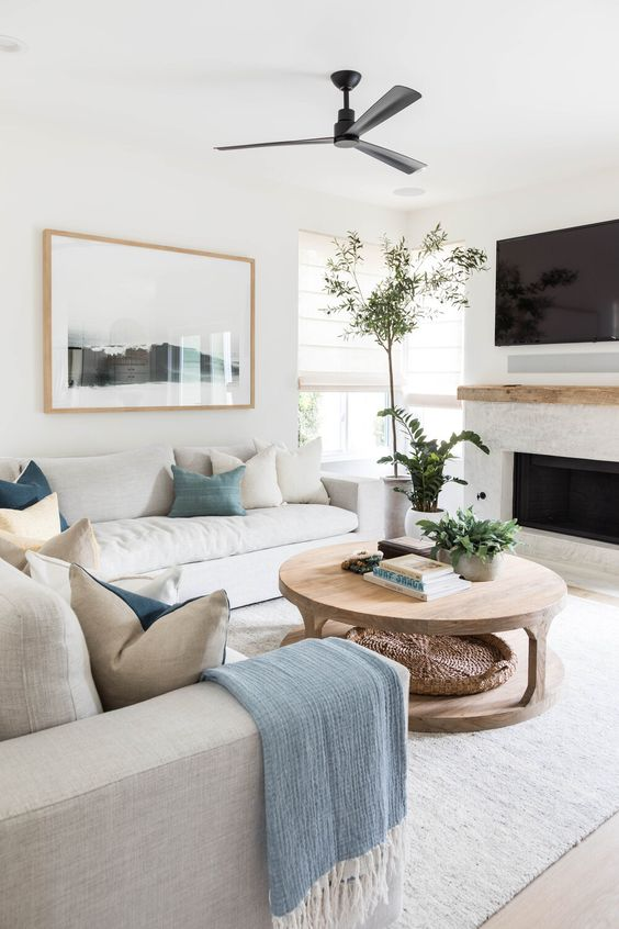 a modern neutral coastal living room with two sofas, neutral and blue pillows, a wooden coffee table and a fireplace