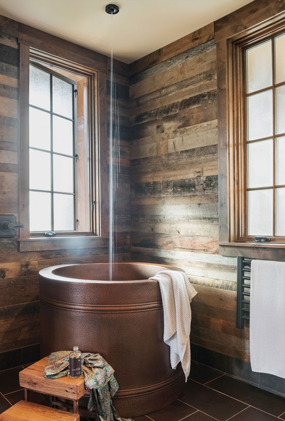 a modern rustic bathroom clad with weathered wood, with a copper Japanese soaking tub and wooden furniture