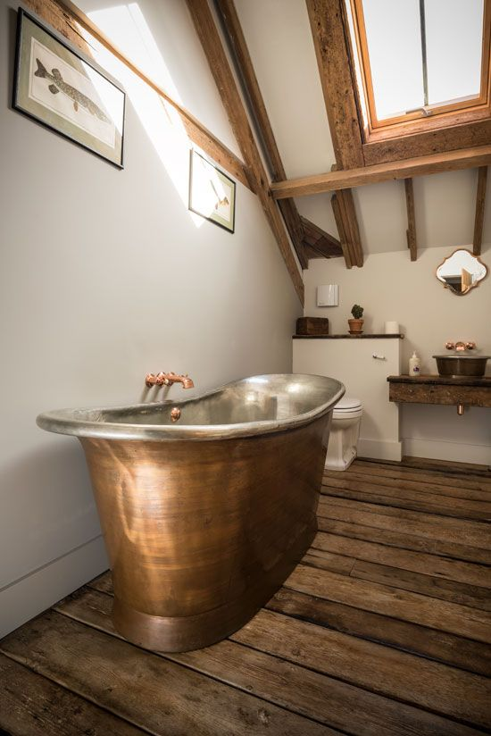 a modern rustic bathroom with wooden beams and furniture and a copper bathtub plus fxitures for a wow effect