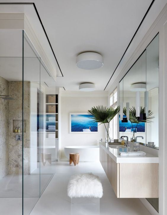 a modern seaside bathroom done in neutrals, with a stone clad shower, a floating vanity, a bright artwork over the tub and neutral linens