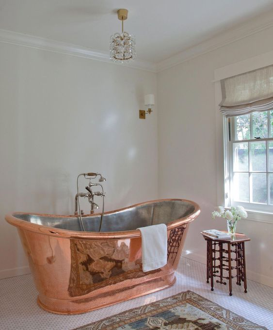a modern sophisticated bathroom in neutrals, with a copper bathtub, a catchy stool, lamp and rug