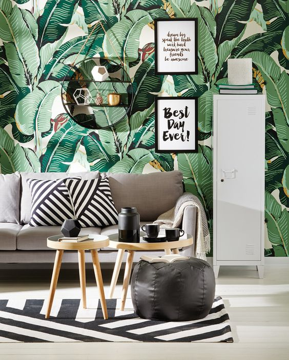 a modern tropical living room with a banana leaf wallpaper wall, a neutral sofa and wooden tables, black and white decor