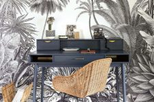 a monochromatic home office nook with a black white tropical wall, a graphite grey desk and woven items