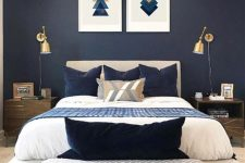 a moody bedroom with navy walls, an upholstered bed, a geometric gallery wall and gold sconces plus a comfy bench