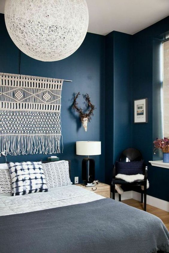 a moody boho bedroom with navy walls, black chairs, a macrame hanging, a woven lamp and printed bedding