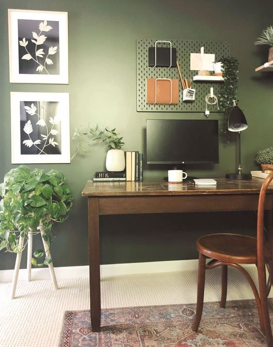 a moody green home office with a hunter green wall, mid-century modern furniture, botanical artworks and potted plants