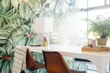 a moody home office with a statement tropical wall, a white desk, leather chairs and some potted greenery is lovely