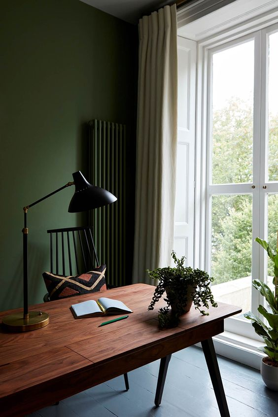 a moody home office with hunter green walls and a radiator, a mid-century modern desk, black lamps and potted greenery