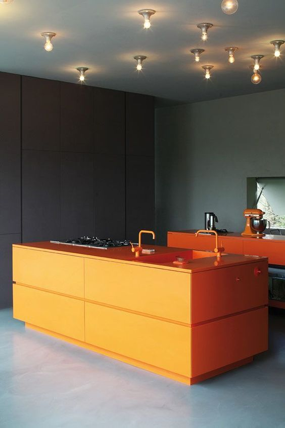 a moody kitchen in black and dark green, with orange cabinets and a kitchen island plus bright orange fixtures