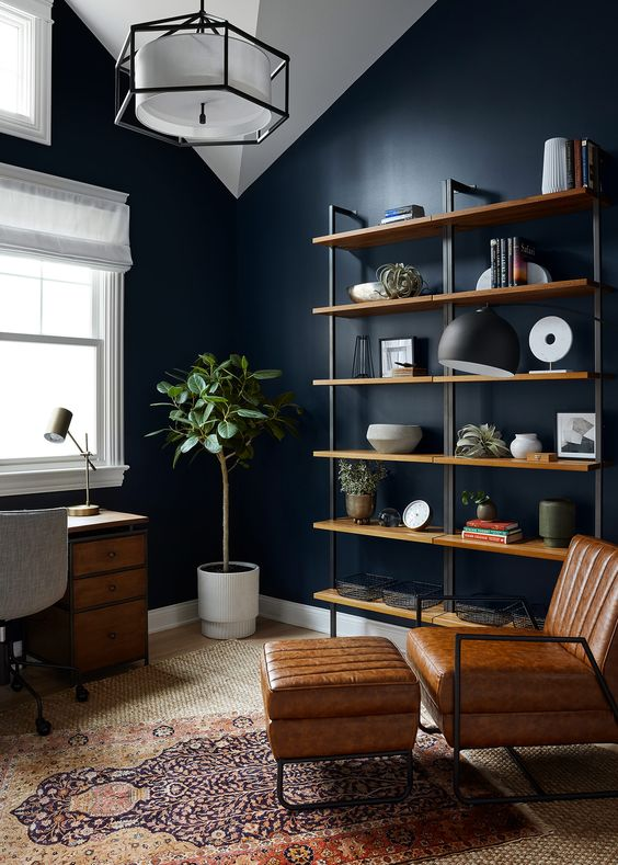 a moody midnight blue home office with industrial furniture, a leather chair and ottoman, a shelving unit and a pendant lamp