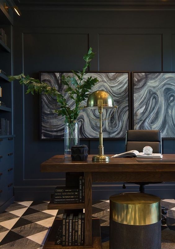a moody navy home office with built-ins, a heavy wooden desk, a leather chair and touches of gold plus a cool gallery wall