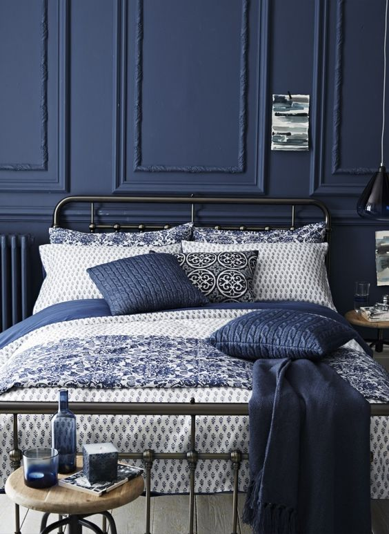 a moody refined bedroom with navy paneling, a black metal bed, vintage stools and navy bedding