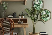 a moody tropical home office with an olive green wall, tropical artworks, a monstera in a basket and a rattan chair