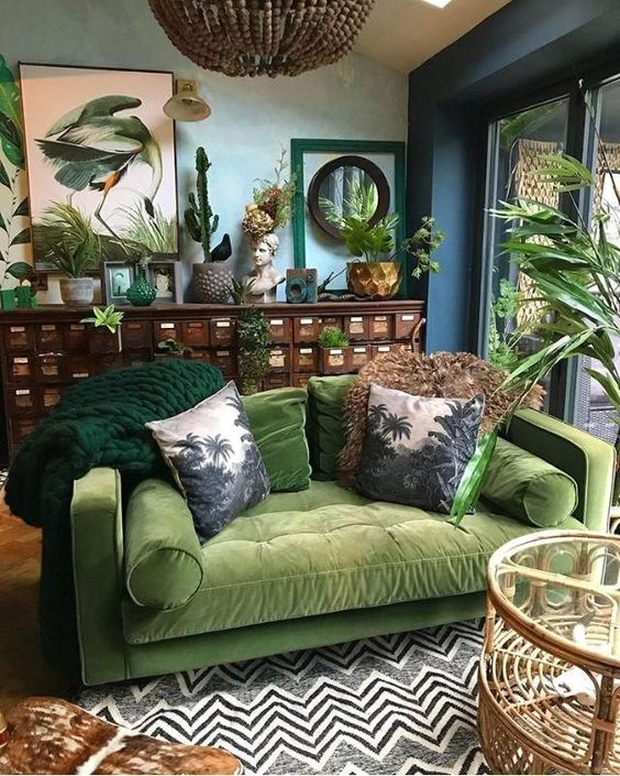 a moody tropical living space with blue walls, a vintage sideboard, a green sofa, a printed rug and bold artworks