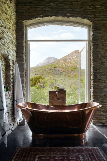 a natural rustic bathroom clad with stone and with a lovely copper bathtub in front of the window is a dream