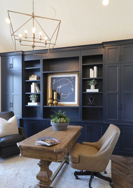 a navy home office with built-in closed and open storage units, an artwork, a catchy gold chandelier and a wooden desk