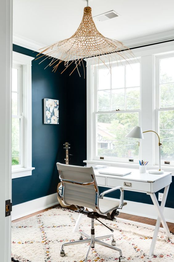 a navy home office with white and tan furniture, a crazy raffia covered lamp and a cool artwork on the wall