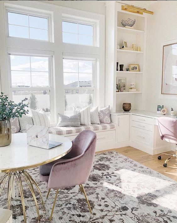 a neutral and a bit pastel home office with printed textiles, lavender chairs, a comfy windowsill bench and gold touches